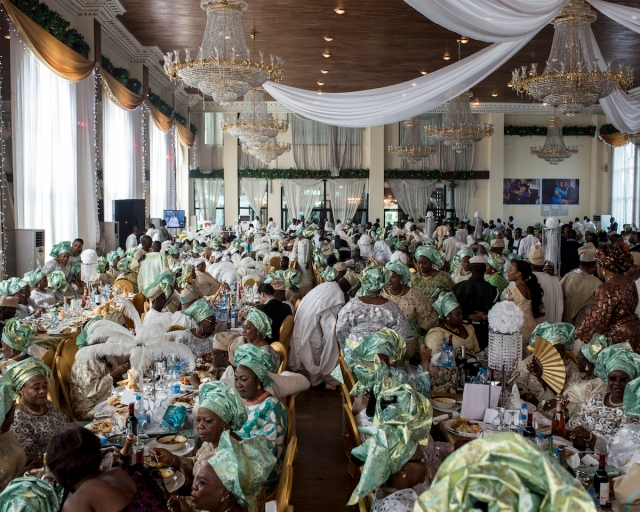 An opulent wedding for nearly a thousand guests was held at the banquet hall of a private housing estate in Lagos, Nigeria. Guests wear matching outfits and hats chosen by the bride's family. © Glenna Gordon, 2014